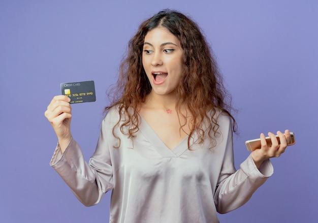 Alegre jovem bonita segurando o telefone e olhando para o cartão de crédito na mão