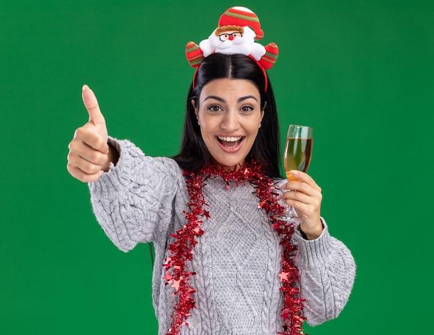 Alegre jovem caucasiana com bandana de papai noel e guirlanda de ouropel em volta do pescoço segurando uma taça de champanhe, olhando para a câmera mostrando o polegar isolado no fundo verde