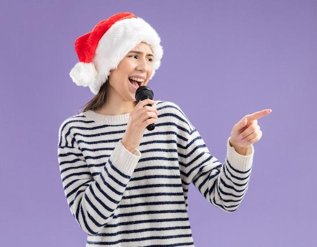 Alegre jovem caucasiana com chapéu de papai noel segurando microfone fingindo cantar, olhando para o lado isolado no fundo roxo com espaço de cópia