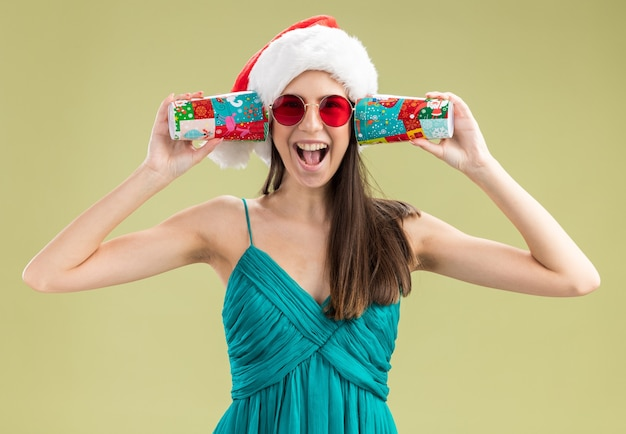 Alegre jovem caucasiana com óculos de sol e chapéu de papai noel segurando copos de papel nas orelhas, isolados na parede verde oliva com espaço de cópia