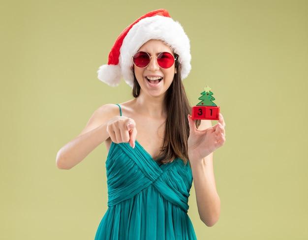 Alegre jovem caucasiana com óculos de sol e chapéu de papai noel segurando um enfeite de árvore de natal e apontando