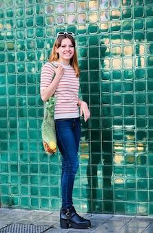 Alegre jovem caucasiana com uma bolsa de rede sobre o ombro com legumes em uma parede verde na rua