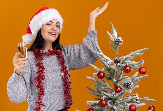 Alegre jovem caucasiana usando chapéu de natal e guirlanda de ouropel em volta do pescoço em pé perto da árvore de natal decorada segurando uma taça de champanhe e mostrando a mão vazia isolada na parede laranja
