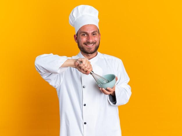 Alegre jovem cozinheiro masculino caucasiano com uniforme de chef e boné batendo ovos na tigela, olhando para a câmera isolada na parede laranja com espaço de cópia