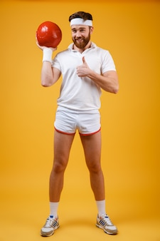 Alegre jovem desportista segurando bola faz os polegares para cima gesto
