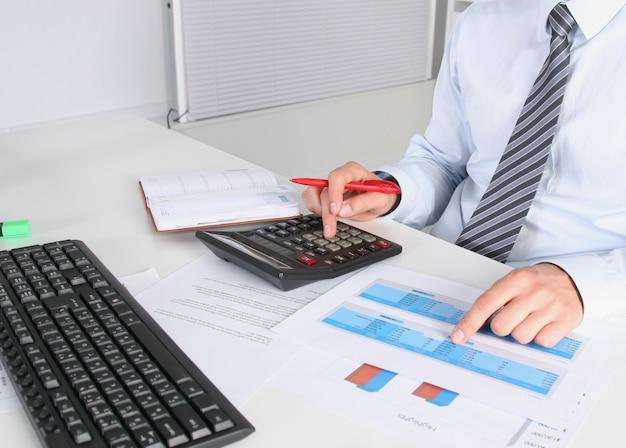 Alegre jovem empresário sentado à mesa com o laptop e alongamento no escritório
