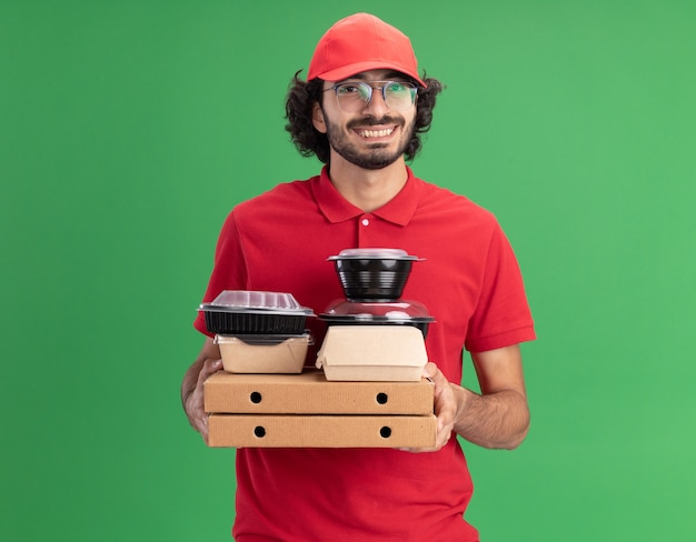 Alegre jovem entregador caucasiano de uniforme vermelho e boné de óculos, segurando pacotes de pizza com pacotes de comida de papel e recipientes de comida neles olhando para a frente