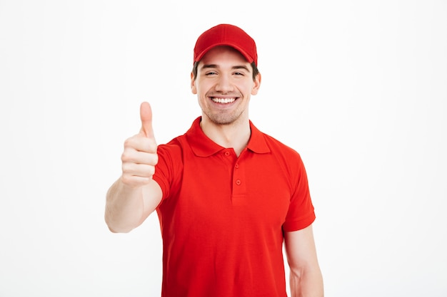 Alegre jovem entregador de boné vermelho com polegares para cima
