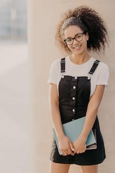 Alegre jovem estudante afro carrega blocos de notas ou diário, veste camiseta branca, sarafan preto