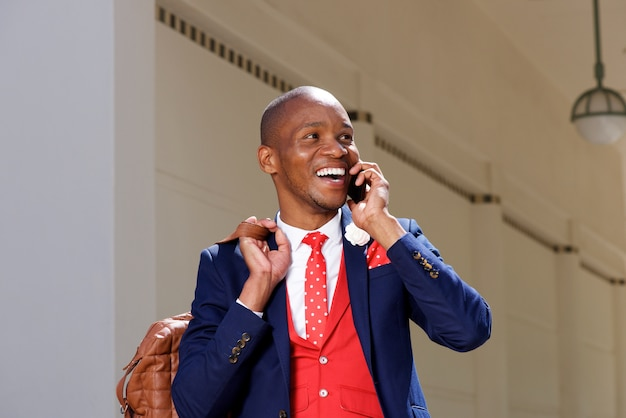 Alegre, jovem, homem africano, em, paleto, falando telefone móvel