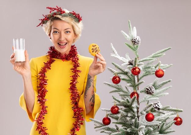 Alegre jovem loira usando coroa de flores de natal e guirlanda de ouropel em volta do pescoço, em pé perto da árvore de natal decorada, segurando um copo de leite e biscoito, parecendo isolado na parede branca