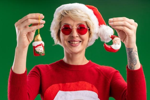 Alegre jovem loira vestindo chapéu de natal e suéter de natal de papai noel com óculos olhando mostrando boneco de neve e enfeites de natal de papai noel isolados na parede verde