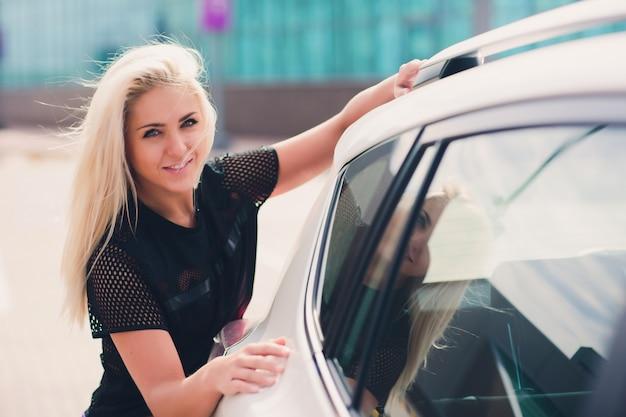 Alegre jovem motorista do sexo feminino abraçando seu carro novo.