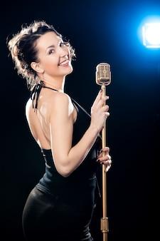 Alegre, jovem, mulher, cantor, segurando, dourado, vintage, microfone, iluminado, projetor