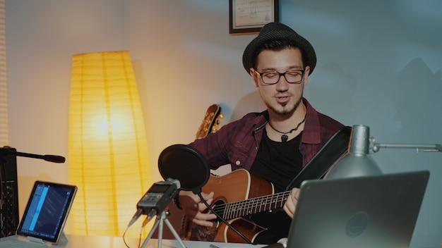 Alegre jovem músico tocando guitarra e cantando no microfone no estúdio em casa
