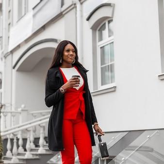 Alegre jovem negra num elegante terno vermelho numa jaqueta longa da moda com uma xícara de café caminha e sorrindo na rua perto de prédio vintage. modelo de garota elegante feliz africana com sorriso fofo na cidade.
