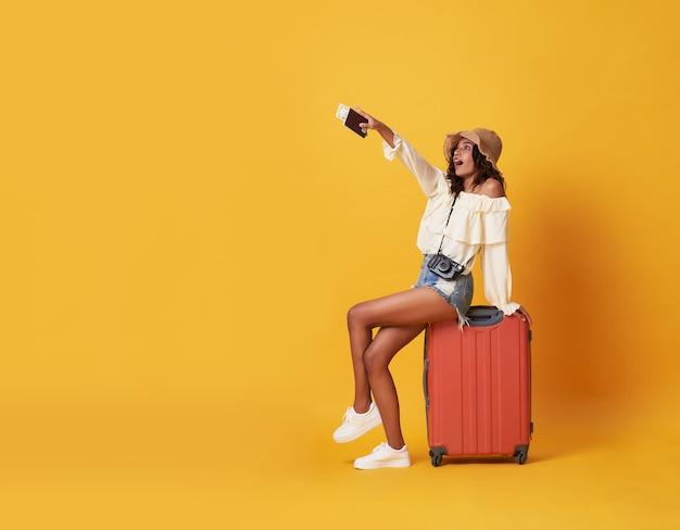 Alegre jovem negra vestida com roupas de verão, sentado em uma mala e apontando o dedo no espaço da cópia