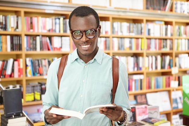 Alegre jovem negro elegante usando óculos em pé na biblioteca com prateleiras de livros