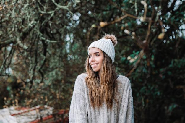 Alegre jovem viajante com chapéu de malha quente e blusa, sorrindo e olhando para longe enquanto descansava na costa borrada com o velho barco