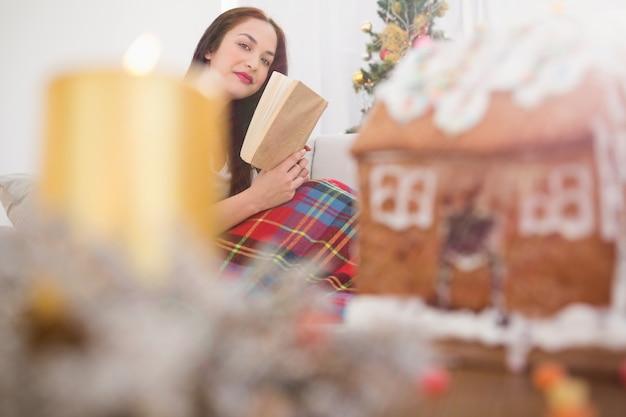 Alegre leitura de morena no sofá com capa no natal