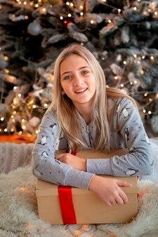 Alegre linda garota adolescente abrindo presentes. criança de pijama se divertindo perto de uma árvore pela manhã