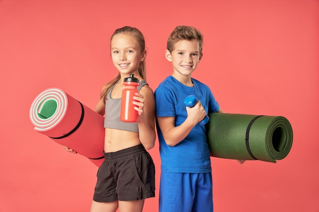 Alegre linda garota com uma garrafa de água olhando para a câmera e sorrindo enquanto o menino segura halteres e tapete de ioga