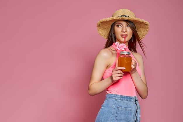 Alegre linda garota da praia com chapéu de verão, posando de maiô corporal com coquetel na mão