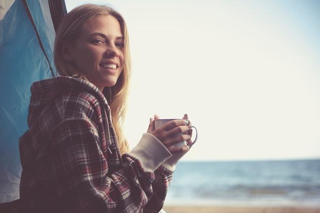 Alegre linda jovem loira viajante segurando uma xícara de bebida de café ou chá dentro de sua barraca, acampando na praia com liberdade e vista para o mar