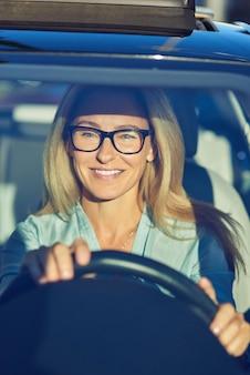 Alegre linda mulher madura ou mulher de negócios usando óculos, dirigindo seu carro moderno