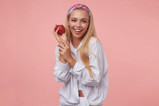 Alegre linda mulher sorrindo amplamente e posando com pêssego na mão, vestindo roupas casuais