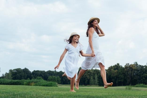 Alegre mãe e filha caminhando na natureza
