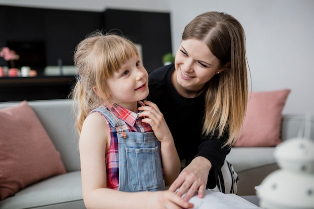 Alegre mãe e filha fazendo lição de casa juntos