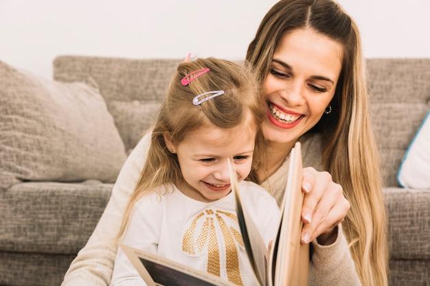 Alegre mãe e filha lendo livro perto do sofá