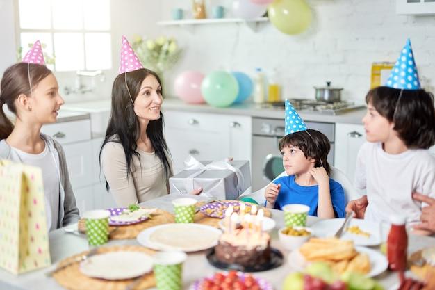 Alegre mãe latina de meia idade segurando a caixa de presente, conversando com seus filhos adoráveis enquanto jantava, comemorando o aniversário juntos em casa. paternidade, conceito de celebração. foco seletivo