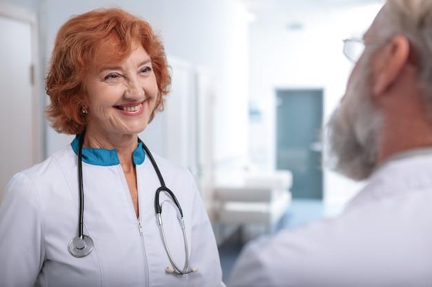 Alegre médica sênior falando com seu colega no corredor do hospital