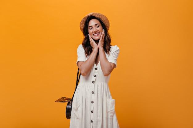 Alegre menina adulta em sorrisos bonitos de vestido branco em fundo laranja. mulher pensativa em pequeno chapéu de palha com bolsa preta posando.