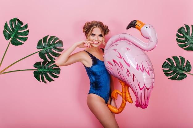 Alegre menina bonita com belo penteado, tocando seu rosto e segurando o pássaro inflável com plantas no fundo. retrato de jovem sorridente em traje vintage posando com flamingo de brinquedo