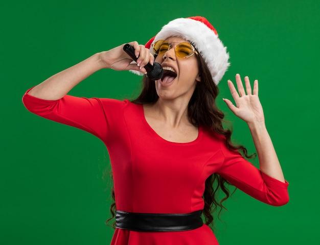 Alegre menina bonita com chapéu de papai noel e óculos, segurando o microfone, segurando a mão no ar, cantando com os olhos fechados, isolado no fundo verde