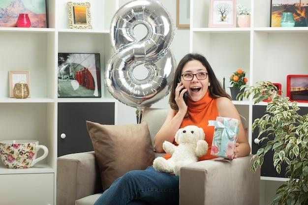 Alegre menina bonita em óculos ópticos falando no telefone e segurando uma caixa de presente, sentada na poltrona na sala de estar em março, dia internacional da mulher