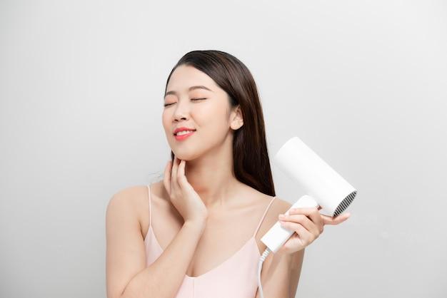 Alegre menina bonita na toalha sorrindo rindo cantando com secador de cabelo, fazendo careta sobre fundo branco. spa de beleza e cosmetologia.