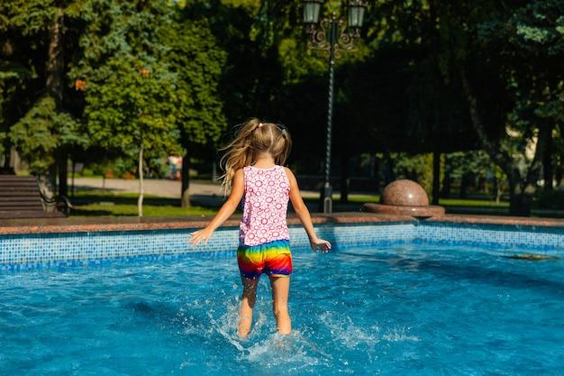 Alegre menina bonitinha está brincando na fonte. a criança está se divertindo em um parque de verão na fonte da cidade.