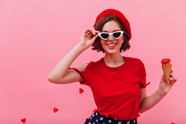 Alegre menina branca em óculos de sol comendo sorvete. jovem atraente na boina, apreciando a sobremesa.