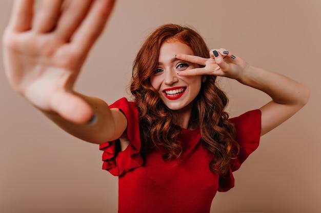 Alegre menina caucasiana com vestido vermelho dançando. mulher jovem e maravilhosa com cabelo ruivo posando com o símbolo da paz.