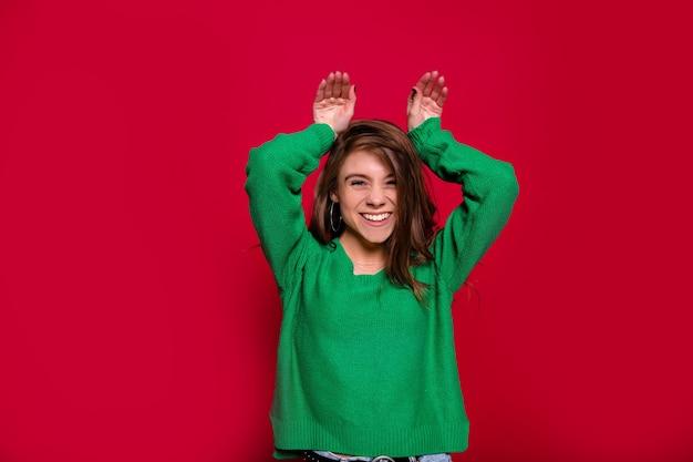 Alegre menina caucasiana expressando emoções positivas, vestida de suéter verde enquanto posava no ano novo em fundo vermelho, com mãos na cabeça. jovem alegre em estúdio