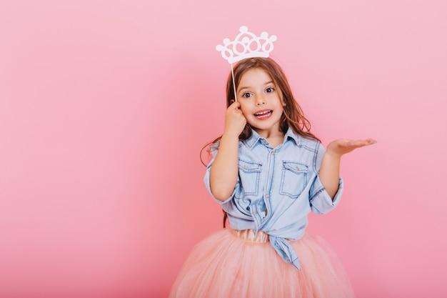 Alegre menina com longos cabelos castanhos em saia de tule, segurando a coroa de princesa na cabeça isolada no fundo rosa. comemorando carnaval brilhante para crianças, expressando positividade da festa de aniversário