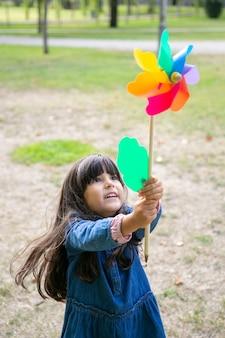 Alegre menina de cabelos negros brincando no parque, segurando e levantando o cata-vento, olhando para o brinquedo de emoção. tiro vertical. conceito de atividade infantil ao ar livre