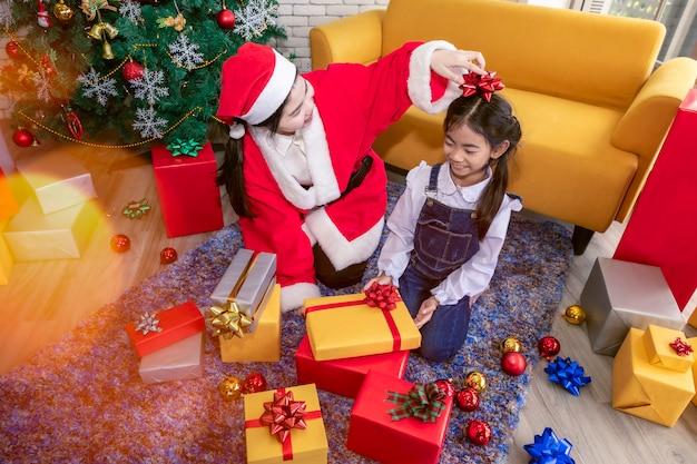 Alegre menina e mãe segurando caixas de presentes de natal.