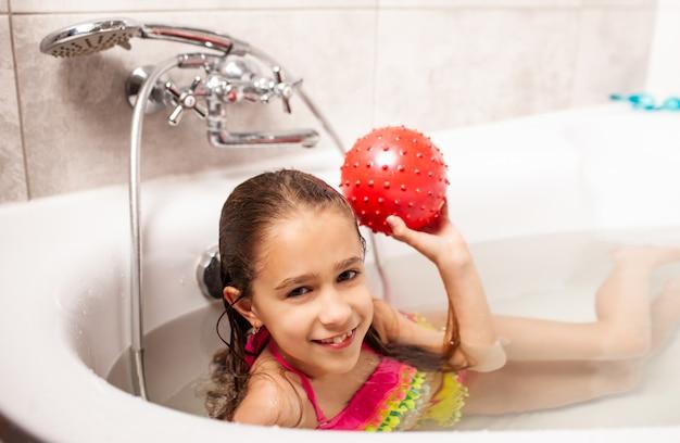 Alegre menina encantadora sorridente banha-se com bola vermelha e olha para a câmera.