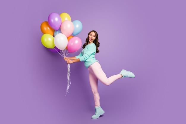 Alegre menina feminina segurar muitos balões desfrutar festivo mulher dia evento grito usar turquesa suéter rosa calçado rosa.