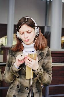 Alegre menina morena bonita em um shopping center se divertindo ouvindo música em fones de ouvido e selecionando músicas do seu telefone